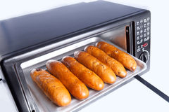 Baked bread in electric oven Royalty Free Stock Image