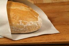 Baked bread in paper. Hot and crunchy freshly baked cob of bread in paper on old wooden table Royalty Free Stock Photos