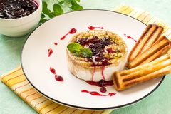Baked brie cheese with cowberry sauce. Brie cheese baked with bread crumbs and thyme. Served with cranberry sauce and grilled bread sticks stock photography
