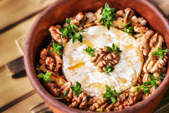 Baked brie cheese with honey, walnuts and thyme Stock Photography
