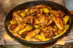 Baked briet Kartoffeln mit köstlichen gebratenes Hühnerflügeln mit der goldenen Kruste, die mit Soßen in der schwarzen Schüssel a stockfotos