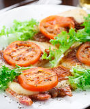 Baked brisket with mozarella and tomato. On a plate Stock Photo
