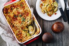 Baked brussel sprout gratin with a bacon and bread crumbs. On wooden background royalty free stock photo