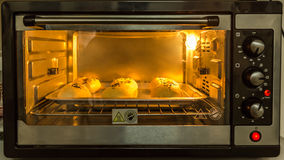 Baked Bun In Front Of Microwave Oven Royalty Free Stock Photo