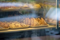 A rich variety of buns pies, donuts in a typical confectionery shop window. Baked buns in the bakery. Sweet dessert food closeup. Baked buns in the bakery stock images
