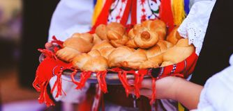 Baked buns or cakes in the hands of the children dressed in traditional costume. Bread in form of snails or pigeons in the red royalty free stock image