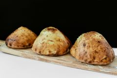Baked buns on a piece of wood. Three baked rolls on a piece of wood stock photo