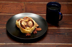 Baked buns on the plate with blue mug. Baked buns with cinnamon and sugar on the plate and blue mug Stock Photography