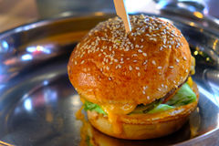Baked burger, junk but delicious. Close up of photo a popular fast food: a classical burger lying on metal pan. You may see quite large fat burger with beef Stock Photos