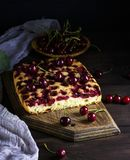 Baked cake with cherries on a brown wooden board Royalty Free Stock Photography