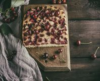 Baked cake with cherries on a brown wooden board Stock Images