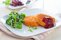 Baked camembert. Breaded and baked camembert with cranberry sauce Stock Images