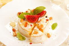 Baked camembert. With fig, honey, nuts and fresh herbs Royalty Free Stock Image