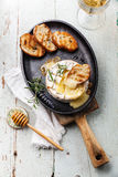 Baked Camembert cheese. With toasted bread on cast-iron frying pan Royalty Free Stock Images