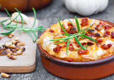 Baked camembert with chorizo  garlic rosemary fried pine nuts Royalty Free Stock Images