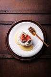 Baked Camembert with fresh figs and honey on a wooden background Royalty Free Stock Photo