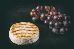 Baked Camembert with grape. On dark table Royalty Free Stock Image