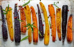 Baked carrots on a baking sheet. With rosemary, coarse sea salt and pepper. Colorful vegetables and spices. Vegetarian dish Stock Photo
