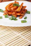 Baked carrots with green onions on a white plate. Organic Vegetarian Food on a bamboo mat Royalty Free Stock Images