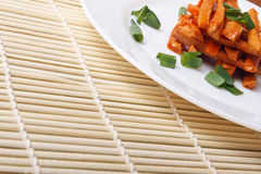 Baked carrots with green onions on a white plate. Organic Vegetarian Food on a bamboo mat Royalty Free Stock Photos