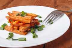 Baked carrots with green onions on a white plate. Organic Vegetarian Food on wooden background Royalty Free Stock Images