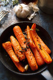 Baked carrots with heavy frying pan on rustic background. Baked carrots with thyme and sea salt on heavy frying pan on rustic background Stock Photos
