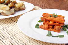 Baked carrots and potatoes with green onions on a white plate. Organic Vegetarian Food on a bamboo mat Royalty Free Stock Photos