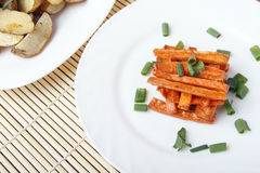 Baked carrots and potatoes with green onions on a white plate. Organic Vegetarian Food on a bamboo mat Royalty Free Stock Photo