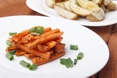 Baked carrots and potatoes with green onions on a white plate. Royalty Free Stock Image