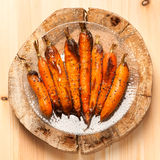 Baked carrots on wooden board in rustic style Royalty Free Stock Photography