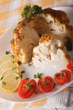 Baked cauliflower and tomatoes, lemons close-up on a plate. vert Stock Photo