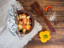Baked in a ceramic bowl of potatoes with chicken meat. Still life in country style on background of old wood and rough Royalty Free Stock Images