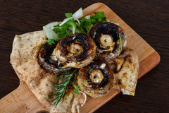 Baked champignons. With rosemary and onion rings abd parsley Stock Image