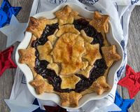 George Washington Cherry Pie With Stars. Baked cherry pie with dough stars and silhouette of George Washington in a white pie pan surrounded by red, white and Royalty Free Stock Photo