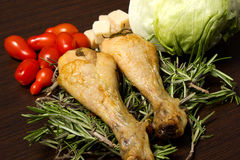 Baked chicken. On table with tomatoes spices and salad Stock Photos