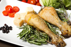 Baked chicken. On table with tomatoes spices, salad and cheese Stock Photography