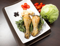 Baked chicken. On table with tomatoes spices, salad and cheese Stock Image
