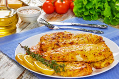 Baked Chicken breas on white plate. Baked Chicken breast coated with melted emmental cheese and Whole-grain mustard on white plate with thyme and lemon slices Stock Image