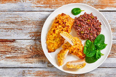 Baked Chicken breas on white plate. Delicious Baked Chicken breast coated with melted emmental cheese and Whole-grain mustard on white plate with red rice, green Stock Photos