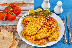 Baked Chicken breas on white plate. Delicious Baked Chicken breast with melted emmental cheese and Whole-grain mustard on white plate with thyme and lemon slices Stock Photos