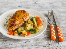 Baked chicken breast with brussels sprouts, onions and carrots on a white plate on wooden surface. stock photos