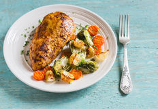 Baked chicken breast with brussels sprouts, onions and carrots on a white plate on wooden surface. Stock Photography