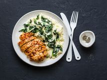 Baked chicken breast, mashed potatoes with creamy spinach on dark background, top view. royalty free stock images