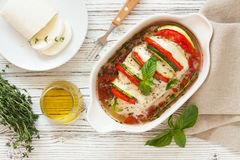 Baked chicken breast stuffed tomatoes , zucchini and mozzarella. Baked chicken breast stuffed tomatoes, mozzarella and zucchini in a white ceramic pan. Top view Stock Photo