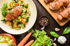 Baked chicken breast wrapped in bacon with boiled potatoes and steamed vegetable garnish Stock Photo