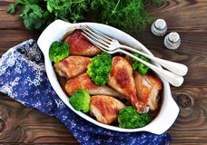 Baked chicken drumstick with organic broccoli on a wooden background. Royalty Free Stock Photos
