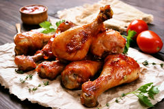 Baked chicken drumstick. On paper, close up view Royalty Free Stock Photo