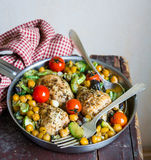 Baked chicken drumsticks with chickpea, courgette, eggplant and cherry tomatoes Stock Image