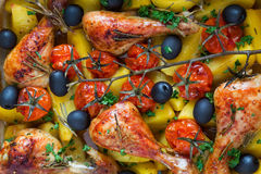 Baked chicken drumsticks, closeup. Cooked with cherry tomatoes, black olives, rosemary and potatoes Stock Photography