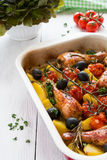 Baked chicken drumsticks in red dish. Cooked with cherry tomatoes, black olives, rosemary and potatoes. White wooden table Stock Image